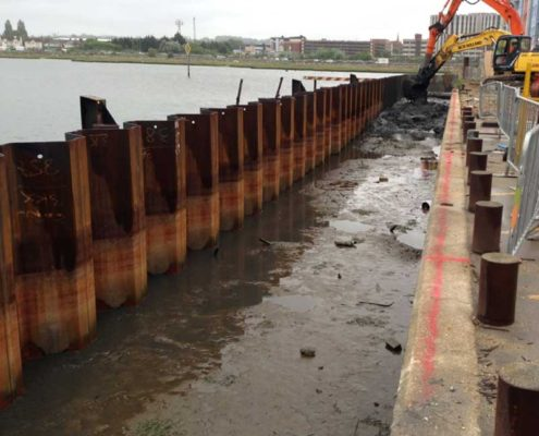 The mixing process taking place between the new quay sheet piles and the existing quay edge. The excavator in the fore front is checking ahead of the main mixing tool to establish depth to the firm sand layer and also to remove any obstructions.